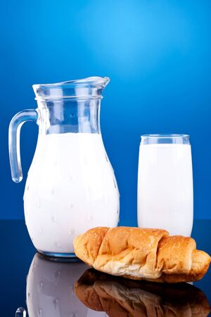 jar and glass of milk near a fresh croissant on blue background photo
