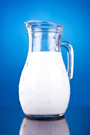 picture of a jar of fresh cow milk on blue background photo