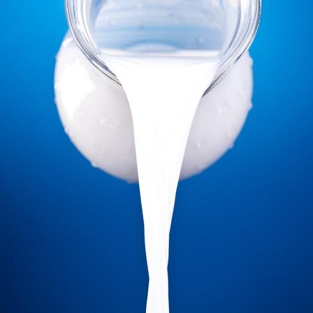 leche y derivados: Primer plano de una jarra con leche derramando sobre fondo azul