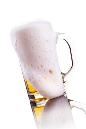 Mug of beer with foam and reflection on white background
