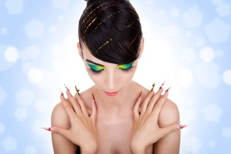 Beautiful portrait of sensual young woman model with glamourbig fingernails, looking down with her hands on her shoulders Stock Photo - 11971722
