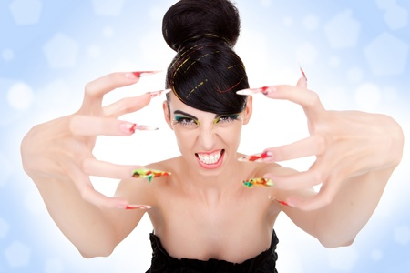 Angry beautiful woman showing her big fancy nails. Portrait of sexy young woman model with glamour make-up and  bright colorful manicure.  photo