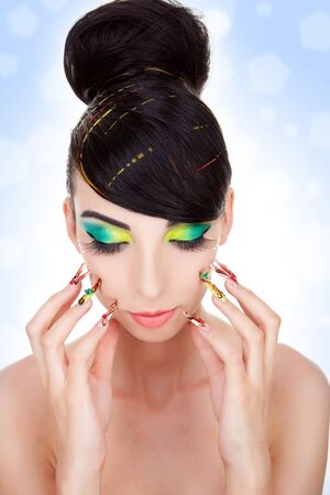 Fashion style, manicure, cosmetics and make-up.  Shiny slicked back hairstyle. Beautiful woman pushing her nails against her face photo