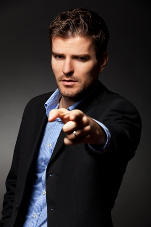 Authoritative, serious business man pointing accusing finger to someone Stock Photo - 12076957