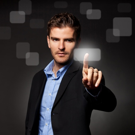 business man pressing a touchscreen button on dark background Stock Photo - 12076920