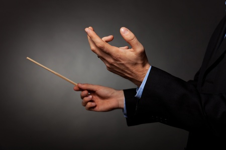 orchestra: Cropped image of a male music conductor directing with his baton in concert  Stock Photo
