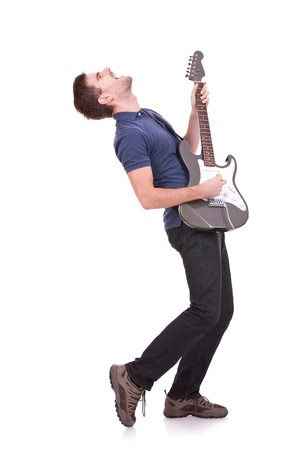 passionate young casual man playing an electric guitar on white bacground photo