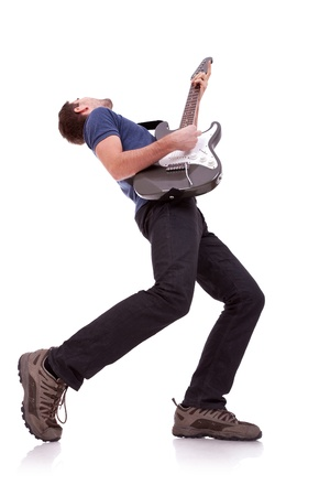 wide angle of a young guitarist playing on white baclground