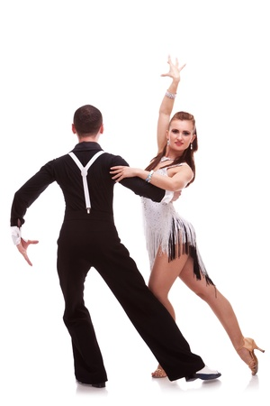 rear view of a male dancer holding his female partner in a difficult dance move. back of a latino dancing couple on white background. passionate latino dancing couple photo