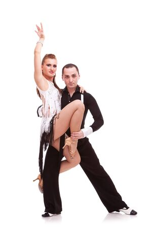 latino couple performing a difficult dance move. latino dancing couple on white background photo