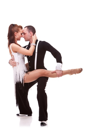 passionate dancing couple on white background. Man holding his woman dance partner in a sensual latino dance move photo