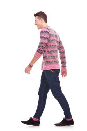 side views: side view of a fashion man walking forward over white . young casual man walking from right to the left of the camera