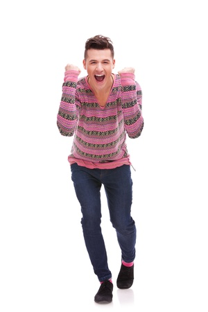 portrait of young man winner gesture against a white background . casual man celebrating a great victory photo