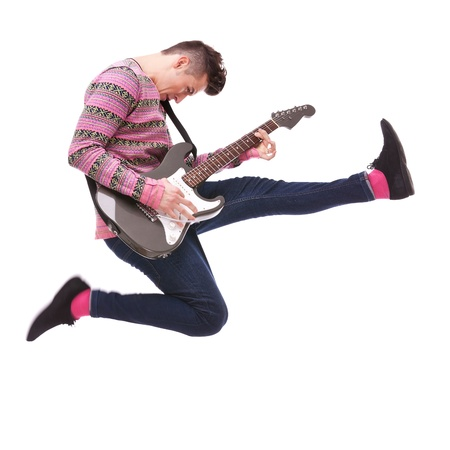 guitars: passionate guitarist jumps in the air on white background. casual man playing an electric guitar and jumping Stock Photo