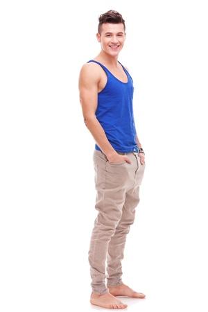 young man standing: a piedi nudi sexy giovane uomo in piedi con le mani in tasca su sfondo bianco