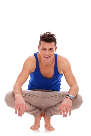 squatting down: View of casual young man squatting down in bare feet on a white background