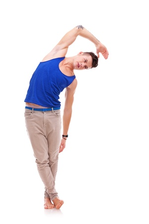 phisical: young man in blue undershirt doing some stretching exercises while standing barefoot on white background