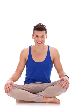 young barefoot man in a yoga position smiling to the camera on white background photo