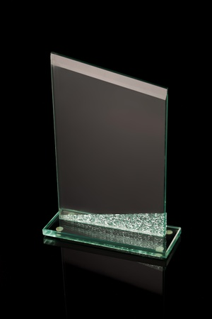 first place award glass trophy on black reflective background photo