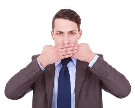 business man making the speak no evil gesture over white . young businessman covering his mouth with his hand photo