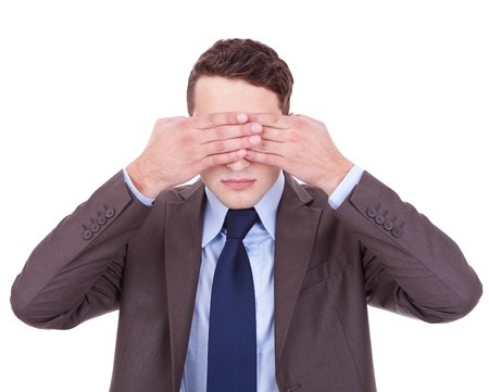 business man making the see no evil gesture over white . young businessman covering his eyes with his hand photo