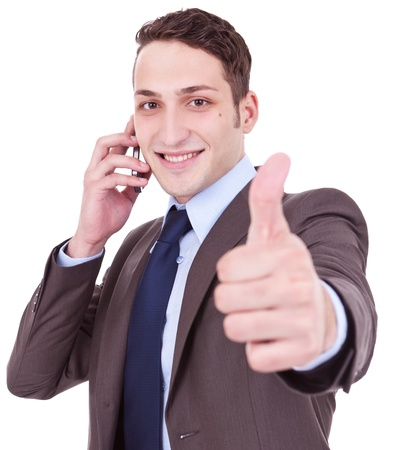 business man showing thumbs up while talking on the phone . all good! good news on the phone photo