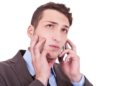 contemplative: Closeup of a contemplative businessman talking on phone - Copyspace on white