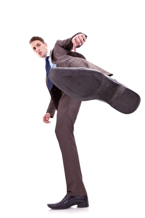 demolishing: young business man kicking something on white background. wide angle shot, view from bellow Stock Photo