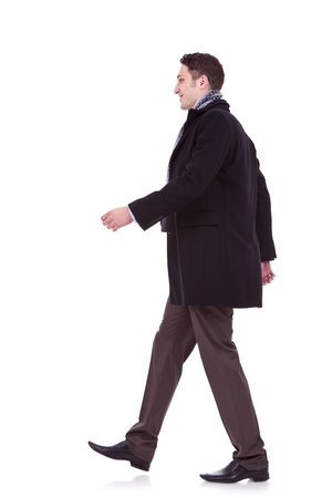 see side: side view of a young business man walking forward on white background