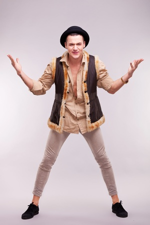 funny young man wearing fur coat and hat welcoming on gray background Stock Photo - 12582107