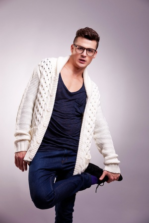 casual man standing on one leg isolated on gray background . fashion model wearing glasses and holding one of his legs photo