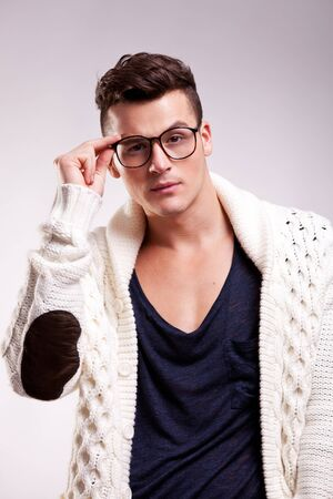 man glasses: Portrait of stylish young man wearing glasses on gray background . fashion male model holding his glasses and looking to the camera