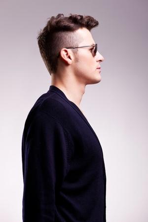 visage profil: photo d'un jeune homme occasionnel des lunettes de soleil sur fond gris