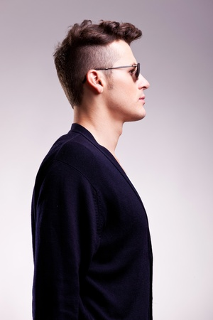 see side: profile picture of a casual young man wearing sunglasses on gray background Stock Photo