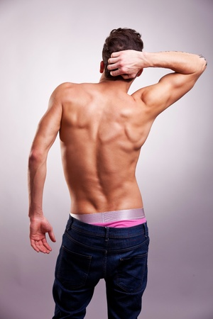 Back of sexy muscular man on gray background. back picture of a shirtless man in a fashion pose photo
