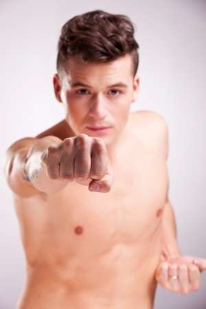 young muscular man in a fighting pose on gray studio background photo