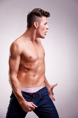 see side: side view of a young muscular fashion model in a dance pose, looking at something on gray background