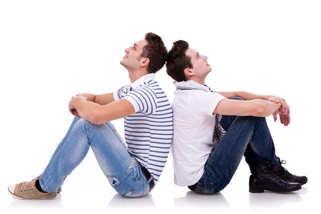 both sides: two young casual men sitting back to back on white background and looking at something on both sides of the picture