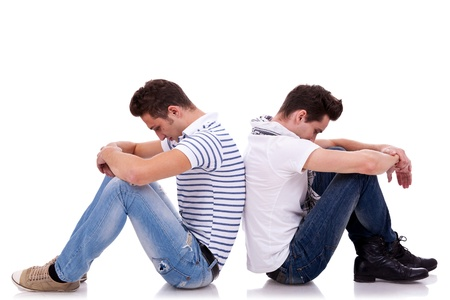 gay couple: two young casual men sitting back to back on white background and looking very sad