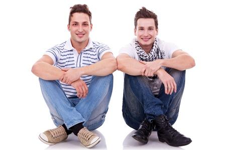 coppia in casa: due amici uomini cercando molto felice, seduti uno accanto all'altro su sfondo bianco