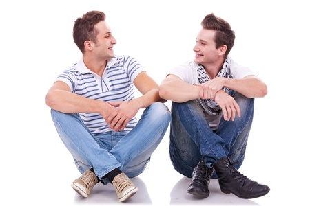 next to each other: two friends smiling to each other while sitting on a white background Stock Photo