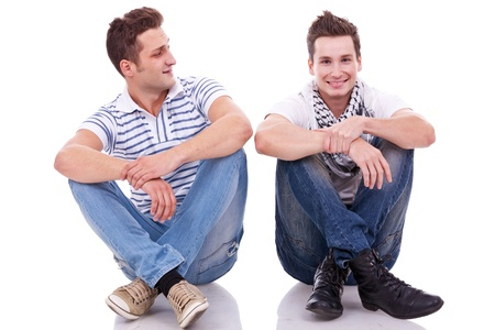 next to each other: two casual men sitting on a white background. one looking at the camera and the other looking at his friend Stock Photo
