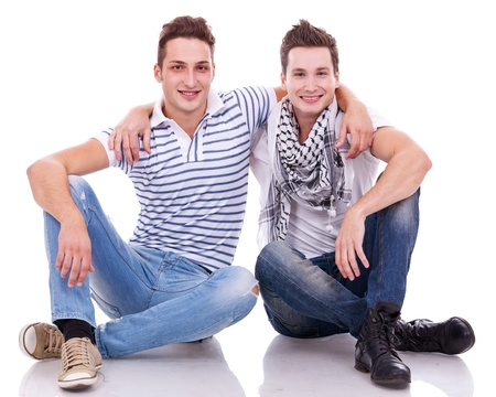 next to each other: two friends smiling to the camera while sitting on a white background.