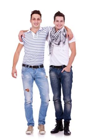 due amici: Raffreddare i due ragazzi amici in piedi con le mani sulle spalle e guardando voi isolato su sfondo bianco