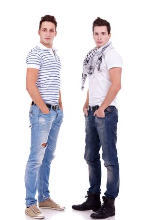 two  friends standing  with their hands in pockets on white background photo