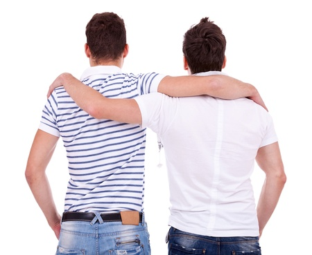 embraced: back view of two friends  standing embraced and looking at something on white background Stock Photo