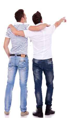 two friends: Back view of  two young men pointing at something. Rear view. Isolated over white background.