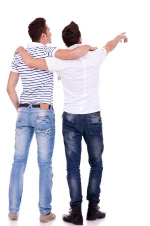 due amici: Vista posteriore di due giovani che puntano a qualcosa. Vista posteriore. Isolato su sfondo bianco.