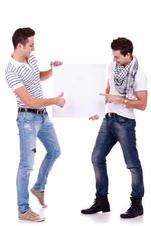 two young men holding a blank board on white background, one pointing to it and one gesturing ok with thumbs up photo