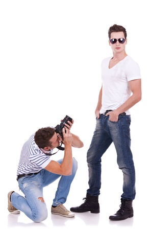 young male fashion model posing for a profesional photographer on white background. young man wearing sunglasses being photographed by a young artist photo